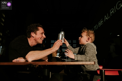 A father and son toast each other as they sit together in a restaurant in this Family Photojournalist Association awarded photo by an Essex, England documentary family photographer.