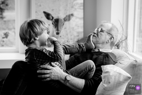 A grandson puts his foot on his grandfather's face as they sit on the couch together in this photo recorded by a Gelderland, Netherlands award-winning, documentary-style family photographer.