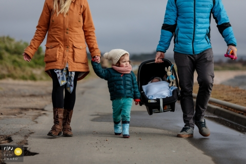 A mother and father take a walk with their infant and young daughter in this FPJA award-winning picture by a Kent, England family photographer.