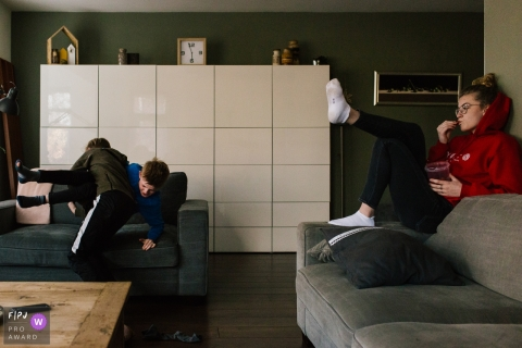 Two boys wrestle on the sofa as their sister watches from the couch in this documentary-style family photo captured by a Netherlands photographer.