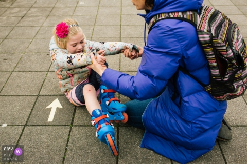 A mother tries to help her daughter up after she falls while rollerblading in this photograph by a Netherlands documentary family photographer.
