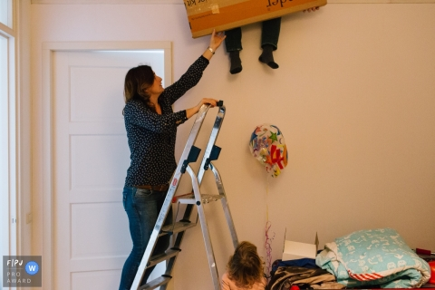 A mother stands on a ladder to grab a box being handed down to her as her daughter watches in this Family Photojournalist Association awarded photo by a Netherlands documentary family photographer.