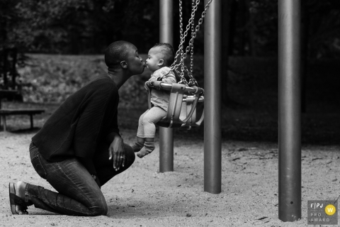 A mother kisses her daughter as she sits in a swing in this FPJA award-winning image captured by a Netherlands family photographer.