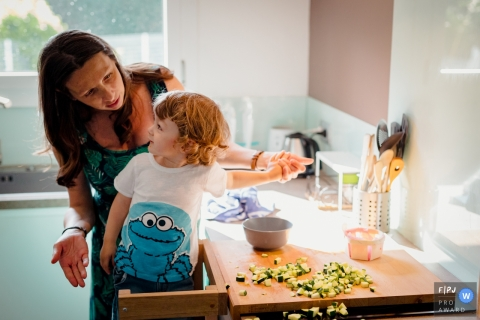 A mother scolds her son for making a mess in the kitchen as she tries to cook in this image created by a Haute-Garonne family photographer.
