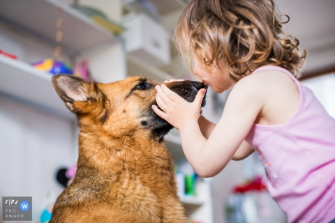A little girl kisses a dog on the nose in this photo recorded by a La Rochelle award-winning, documentary-style family photographer.