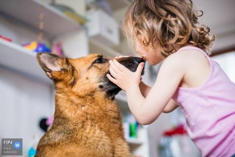 Une petite fille embrasse un chien sur le nez sur cette photo enregistrée par un photographe de famille de style documentaire primé à La Rochelle.