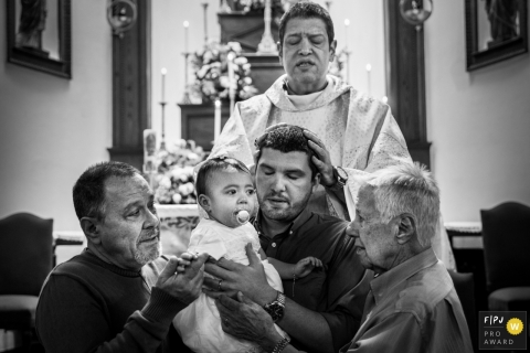 A father holds his baby during a blessing as a priest lays his hands on his head in this photograph created by a Rio de Janeiro, Brazil family photojournalist.