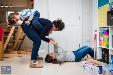 A mother bends down to her daughter who lays on the ground while her son holds onto her back in this documentary-style family photo captured by a Cambridgeshire, England photographer.