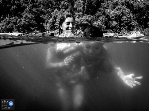 Une mère et son fils nagent ensemble dans un lac sur cette photo réalisée par un photographe de famille primé à Florianopolis.