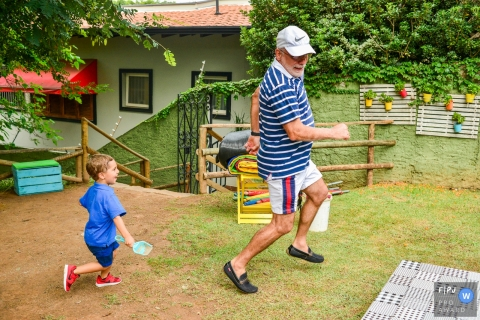 A grandson chases his grandfather outside in this Family Photojournalist Association contest awarded photo created by a Campinas family photographer.