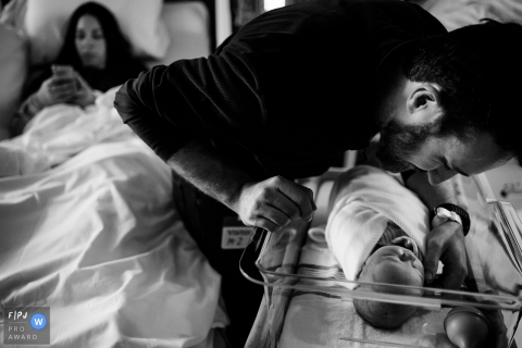 A father checks on his newborn in the hospital as his wife lays in the hospital bed next to them in this black and white birth photo captured by a Washington photographer.