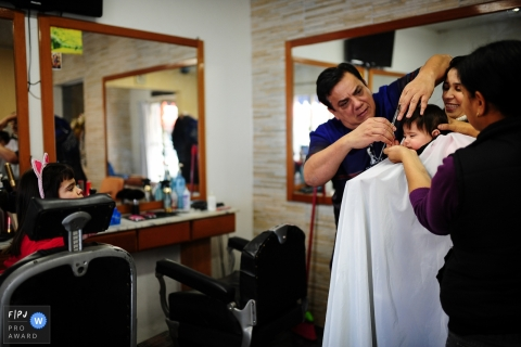 A family stands around a little boy as he gets his hair cut for the first time in this Family Photojournalist Association awarded photo by a Rio Grande do Sul, Brazil documentary family photographer.