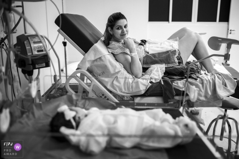 This black and white photo of a mother admiring her newborn daughter across the hospital room was captured by a Brazil documentary family photographer