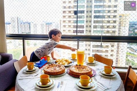 A little boy reaches across a table for the pitcher of orange juice in this award-winning photo by a Goiania family photographer.
