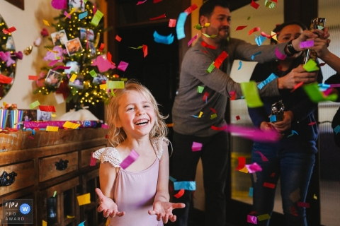 A little girl smiles as confetti falls around her in this photo by a Seattle, WA award-winning family photographer.