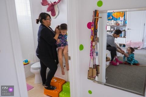 Une mère coiffe les cheveux de sa fille pendant que son mari réconforte leur autre fille qui pleure sur cette photo créée par un photojournaliste de la famille de Los Angeles, en Californie.