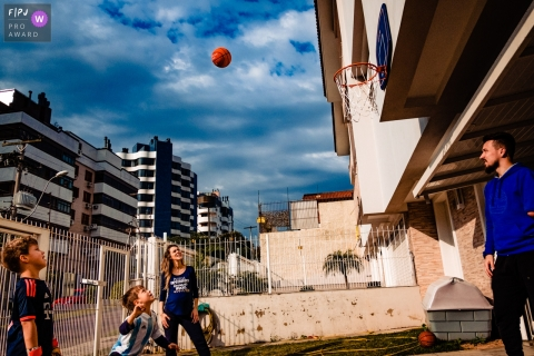 A family plays basketball together outside their house in this documentary-style family image recorded by a Rio Grande do Sul, Brazil photographer.