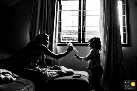 A mother and daughter play with a paper airplane in this Family Photojournalist Association contest awarded photo created by a Rio Grande do Sul, Brazil family photographer.