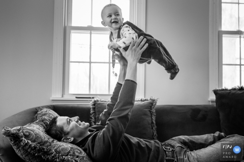 A father lays on the couch and holds his baby boy up in the air in this family picture by a Connecticut photographer.