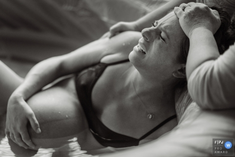 A woman holds her stomach as she gives birth in her birthing tub in this award-winning image captured by a Philadelphia birth photographer.