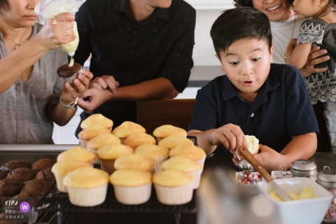 A boy helps frost cupcakes with his family in this FPJA award-winning image captured by a Los Angeles, CA family photographer.
