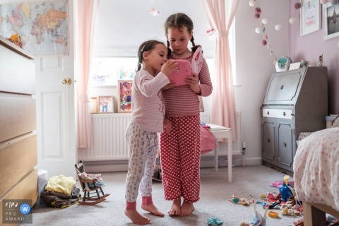 Gloucestershire family photography | Sisters huddle around a mobile device in their bedroom.