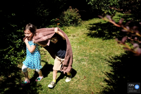 Gloucestershire Family Photograph of siblings running through the garden with a towel over their heads.