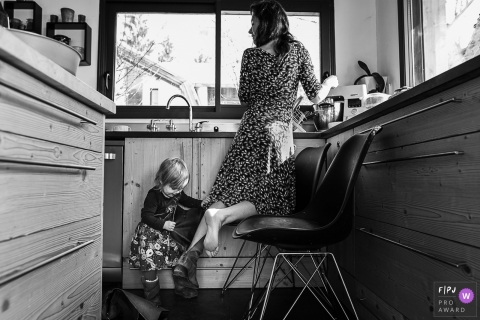 Savoie Family Photography of a young girl taking her mom's boot off during the kitchen chores.