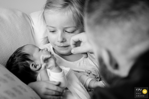 Nantes Family and Birth Photographer | Emotion of a girl holding her little baby sister as dad wipes her tears.