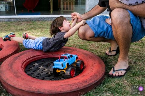 Un photographe de Minas Gerais documente la famille dans leur routine - un père aide son fils dans un moment de frustration à Belo Horizonte