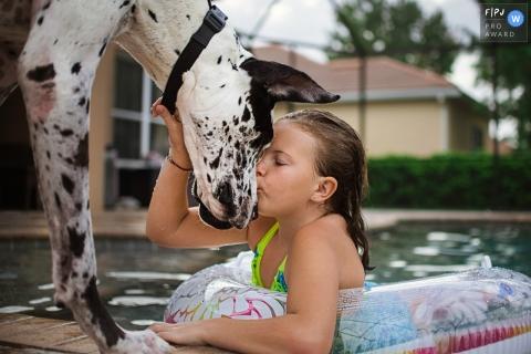 Photographie de famille Sarasota | Florida Poolside chiot bisous avec une fille et son chien