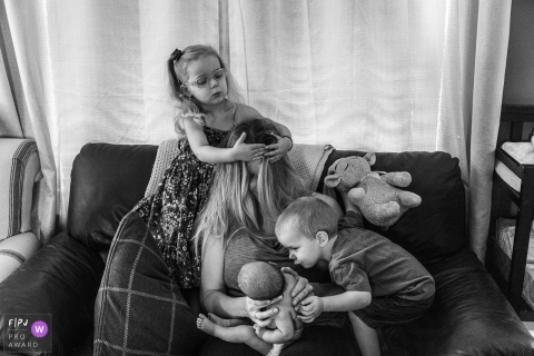 Ontario mother holds baby while boy reaches to kiss baby and girl styles mother's hair | Canada family photojournalism session.