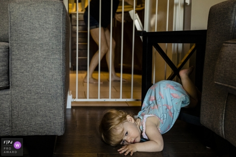 Ontario family photography in Canada - Photo session - toddler lies on floor with legs tangled in table