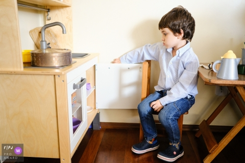 Rio Grande do Sul Family Photography | Boy playing kitchen, looking bored at the cupboard as if thinking, what am I going to cook?
