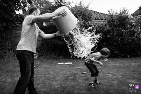Cambridgeshire England family photojournalism in the backyard during a father and son water fight.