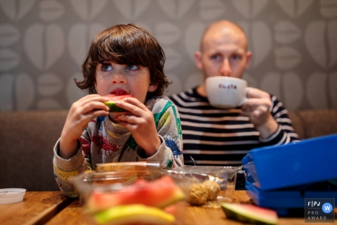 England family reportage photography of a coffee break and chomping on a watermelon slice