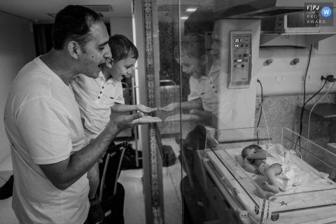Documentary birthing photography in Recife - Pernambuco dad and big brother see newborn baby behind glass.