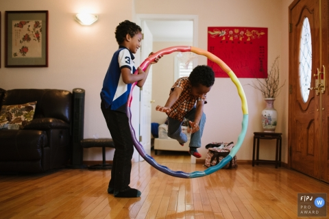 Los Angeles brothers jumping through hula hoop at home during this California family photo session.