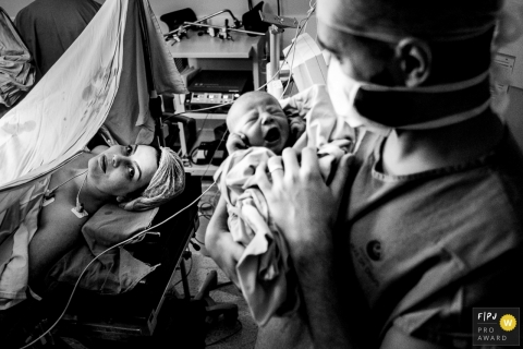 Rio Grande do Sul black and white photos of hospital birthing in Brazil - dad holding newborn baby