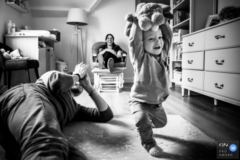Parents hang out with toddler child as he takes his first steps | Belgium Family Session