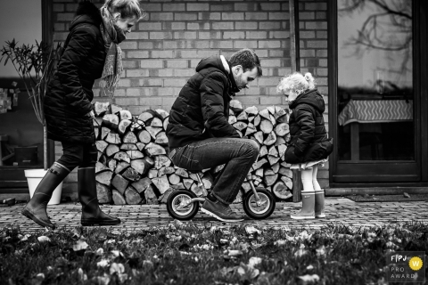 Dad is trying to ride a small bike as his daughter watches | Belgium Family Session