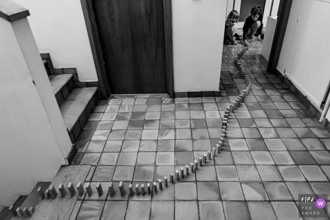 Children line up dominos on the floor through the house | Brabant Wallon Family Photographer