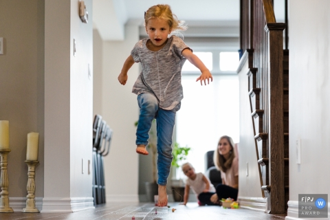 Girl jumps over hurdles in hallway during a game with family | Ontario Family Photographer