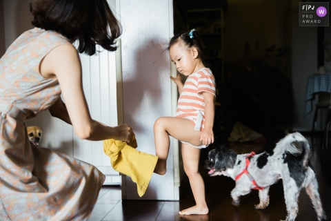 Mother puts clothes for the baby, and two dogs are also onlookers | China Photography for Families