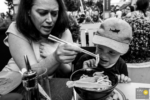 England family photoshoot: Mom trying to feed her son in at a Wagamama restaurant in London