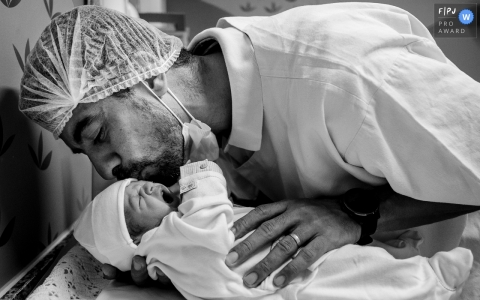 Daddy kisses newborn baby after Mato Grosso hospital delivery
