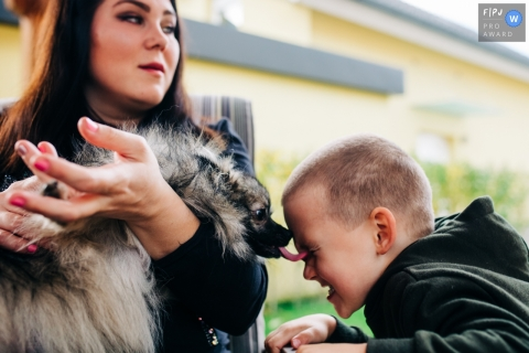 Dog kisses a young boy's face with a nice lick of his tongue | Slovenia Family Photographer