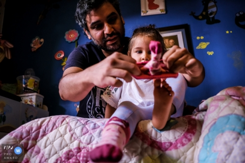 Father helping daughter put on her socks | Talca, Chile Documentary Family Photographer