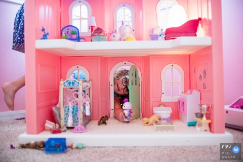 SarasotaFlorida Family Photography Session of two sisters playing with their dollhouse, passed down from their mother.