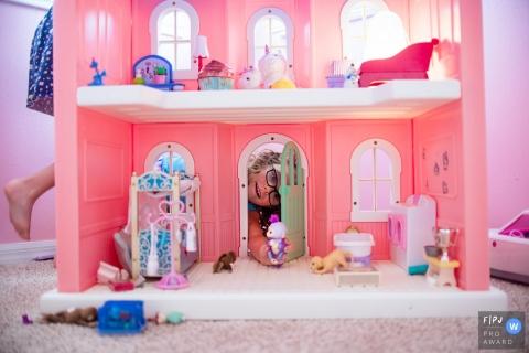 Sarasota Florida Séance de photographie familiale de deux soeurs jouant avec leur maison de poupée, transmise par leur mère.